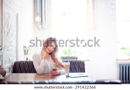 Youth and technology. Young attractive long hair woman using smartphone while sitting at cafe. - stock photo