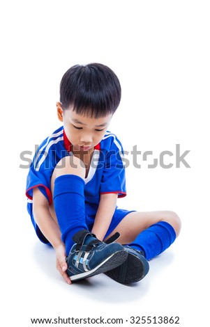 Youth asian soccer player in blue uniform tying shoe before playing soccer with drop shadow.Child preparing ready for competition. Sport lifestyle. Isolated on white background. Studio shot. Full body