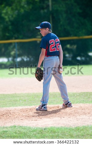 Youth baseball boy pitching on the mound during a game - stock photo