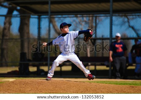 Youth baseball pitcher in wind up wearing white jersey. - stock photo