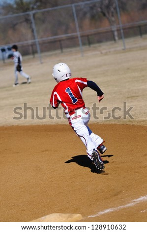 Youth baseball player round first base. - stock photo