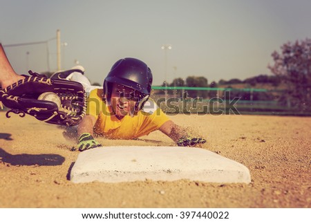 Youth Baseball playing sliding back to base. Focus on glove and ball - stock photo