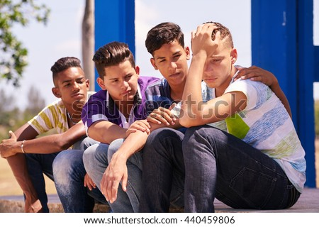 Youth culture, young people, group of male friends, multi-ethnic teens outdoor, teenagers together in park. Boys comforting sad friend, kids helping depressed boy. Adolescence bond, relationship - stock photo