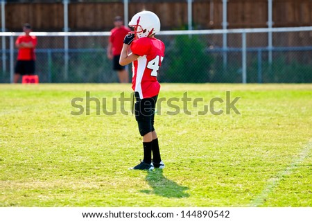 Youth football player on the field - stock photo