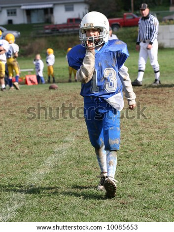 Youth Football Player Walking Off Field During Game. - stock photo