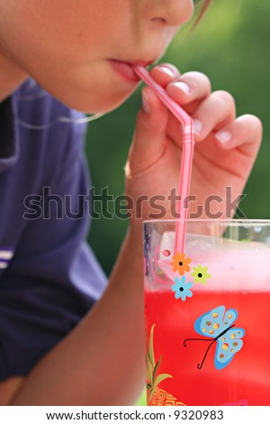 Youth girl drinking juice from straw - stock photo