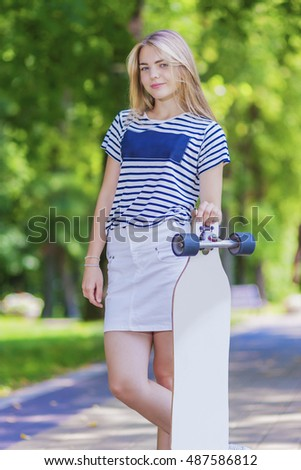 Youth LIfestyle Concepts. Blond Caucasian Teenage Girl Posing With Long Skateboard in Green Forest. Horizontal Shot