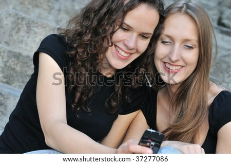 Youth lifestyle - two smiling friends (girls) outdoors with mobile phone - stock photo