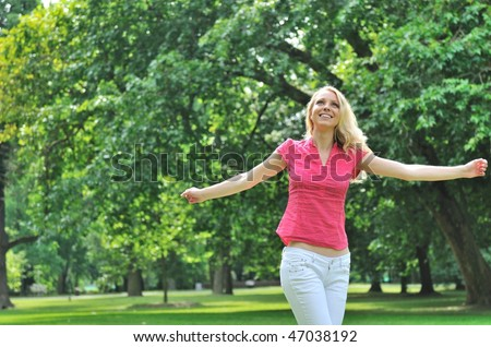 Youth lifestyle - young woman enjoying life outdoors with blurred trees in background - stock photo
