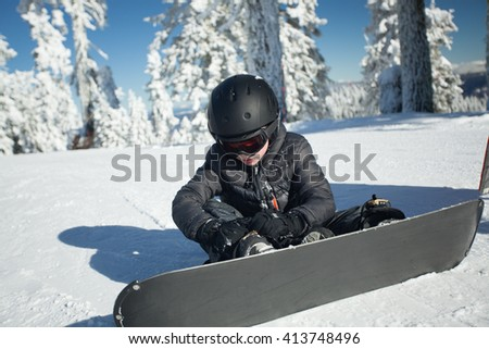 Youth snowboarder tightening his bindings - stock photo