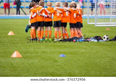 Youth soccer football team. Group photo. Soccer players standing together united. Soccer team huddle. Teamwork, team spirit and teammate example. - stock photo
