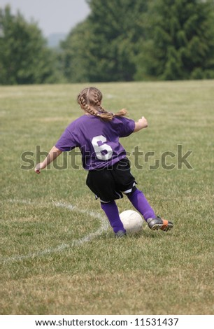 Youth Soccer Player Chasing Ball down field during game. - stock photo