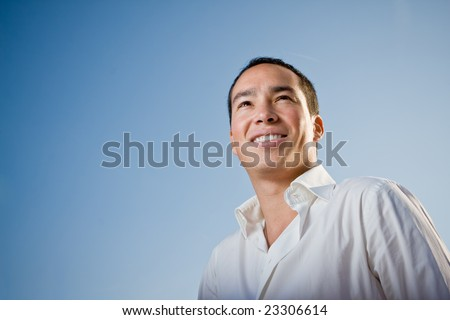 Youth standing against blue sky looking forward - stock photo