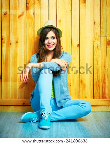 Youth style portrait of young woman sitting on a floor. Teenager girl portrait. Wooden background. - stock photo