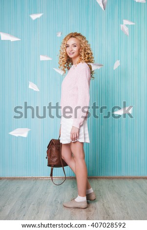 youth traveler women with curly hair and braces pose and smile on blue background. Paper airplanes behind. Concept travel, vacation, holiday