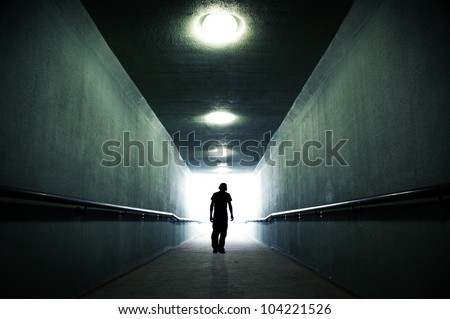 Youth walking into the light - stock photo