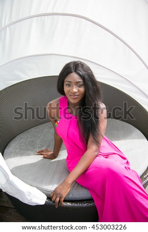 Youthful African woman relaxing by the pool on summer holidays.
