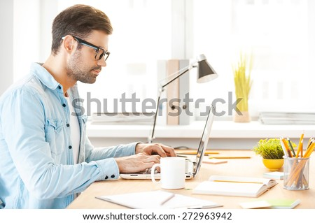 Youthful focus on great solution. Side view of handsome young man in shirt and eyewear working on laptop while sitting at his working place - stock photo