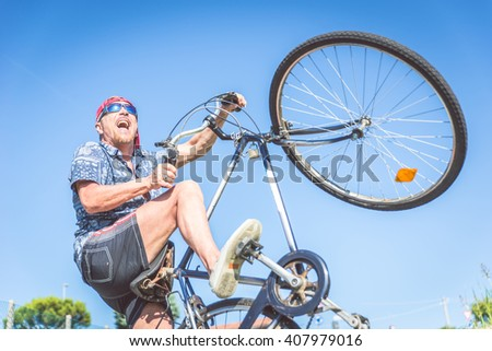 Youthful senior man riding on bicycle and doing a wheelie - Old man acting like a kid - stock photo