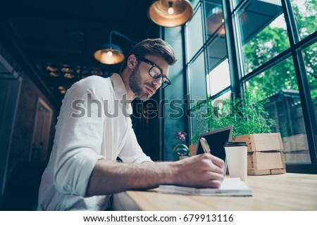 Yow angle view of a young stylish well dressed author writer is working in a modern coworking, writing the novel, in glasses, so serious and focused