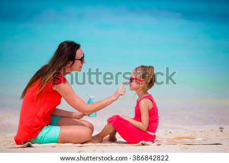 Ypung mother applying sun cream to daughter nose - stock photo