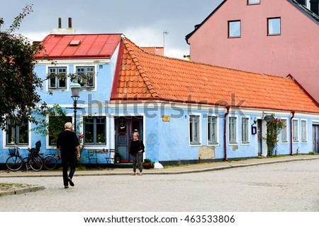 Ystad, Sweden - August 1, 2016: Old blue house in the corner of a street (Pilgrand) in the city. Small table and chairs under window. Bikes parked outside. People walk by on street.