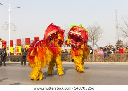 YU COUNTY CHINA FEBRUARY 5: People performing traditional lion dance for celebrating Lantern Festival on February 5 2012 in Yu County, China.  - stock photo