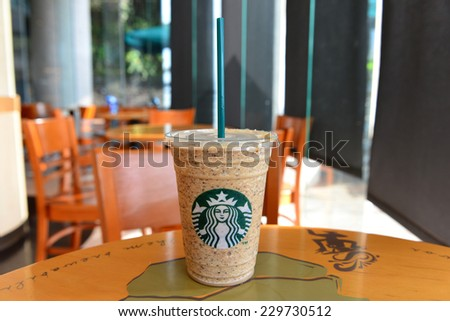 Yuchi, Nantou, Taiwan - October 26, 2014: Glass of Starbuck Coffee Frappuccino Blended Beverages served at wood table in starbuck shop in Taiwan. - stock photo
