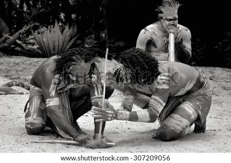Yugambeh Aboriginal warriors men demonstrate fire making craft during Aboriginal culture show in Queensland, Australia. - stock photo