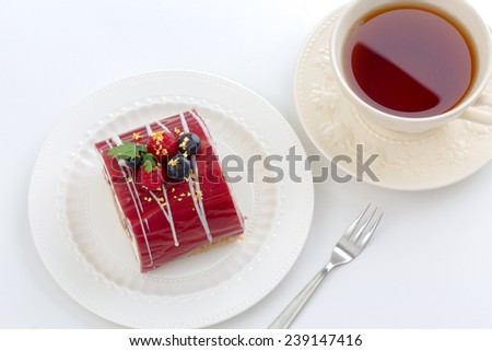 Yule log of white chocolate mousse, stuffed with raspberry puree sponge rolls, glazed with raspberry jelly, garnished with white chocolate, fresh berries, and gold leaf (also know as Buche de Noel) - stock photo