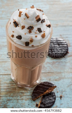 Yummy cocktail with ice cream and milk mixed together. Cocoa and cookie crumbles for taste. Whipped topping as a decoration. Pieces of chocolate cookies on the wooden table. - stock photo