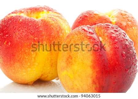 yummy looking wet peaches on white background with water drops - stock photo