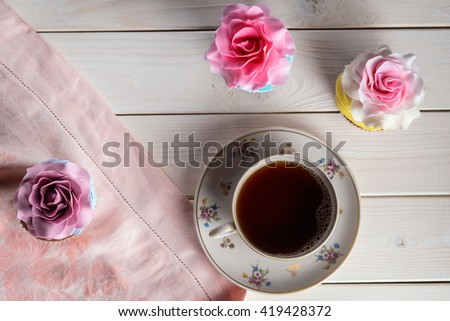 Yummy lunch includes three desirable cupcakes with interesting decoration. Marchpane roses with eatable petals on the top of bakery. The cup of tea on white wooden table. Vintage still life. - stock photo