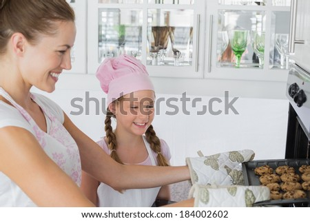 Yung girl looking at mother remove cookies from the oven in the kitchen - stock photo