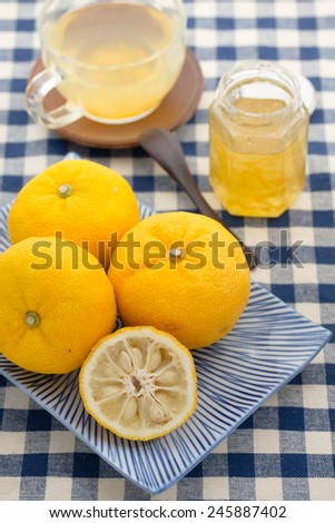 Yuzu cha or Yujacha (citron tea) is a traditional Korean tea (herbal tea) popular in Japan made from the citrus fruit yuzu. Honey combined with aromatic zest of yuzu to make syrup for the drink. - stock photo
