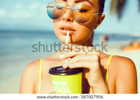 yyoung beautiful brunette girl in sunglasses with beautiful skin and lips, posing on the beach, drinking fresh morning smoothies, fruit juice,cocktail fashion outdoor, close up, cute, , pretty woman - stock photo