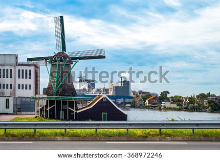 Zaandam, Holland - July 25, 2014: Waterland district,  a traditional wind mill in front of the industrial area