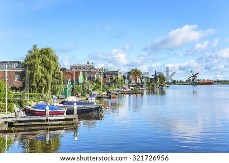 Zaanse Schans. Picturesque view of a Dutch village with old windmills and boats located at the river. - stock photo