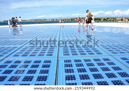 ZADAR - AUG 25: People walking on Greeting to the Sun sculpture. It consists of 300 multilayer glass panels and uses solar power to create a light show at night. On Aug 25, 2014 in Zadar, Croatia - stock photo