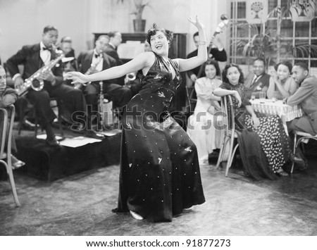 Zaftig woman performing a dance in front of a group of people in a restaurant