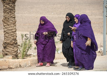 ZAGORA, MOROCCO, MARCH 8, 2014. Muslim women with long gowns walking in Zagora, Morocco, on March 8th, 2014. - stock photo