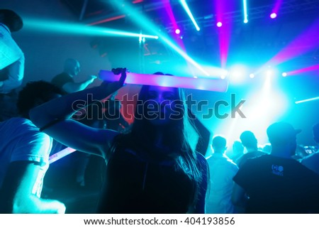 ZAGREB, CROATIA - APRIL 9, 2016 : A woman from the audience with an illuminating stick posing on La Fiesta Stage by Sensation party in Hypo center in Zagreb, Croatia. - stock photo