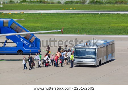 ZAGREB, CROATIA - APRIL 28, 2013:  Passengers leaving airport bus and boarding the plane at Pleso Airport.