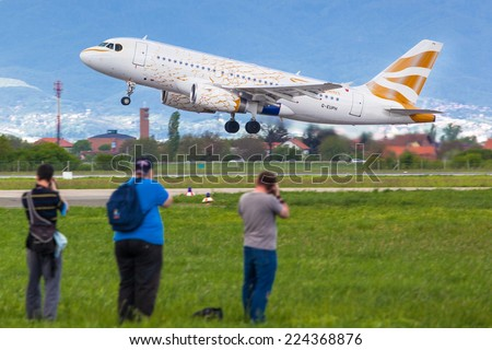 ZAGREB, CROATIA - APRIL 28, 2013: Plane spotters taking photos of British Airways Airbus A319 decorated for London Olympics 2012 to look like golden dove during takeoff from Pleso airport runway. - stock photo