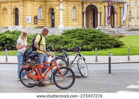 ZAGREB, CROATIA - APRIL 26, 2015: Young mixed race couple standing by the parked bicycles in Zagreb city center, in front of Croatian National Theater, preparing to ride their bikes.
