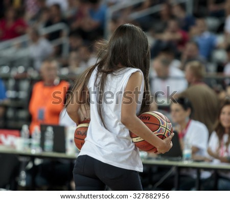 ZAGREB, CROATIA - AUGUST 28, 2015: The preparatory match ahead of the EuroBasket 2015 between Croatia and Israel. Girl carrying two basketball balls