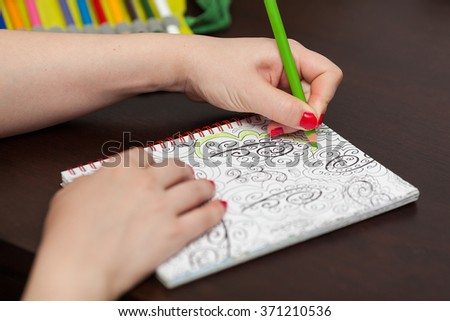 ZAGREB, CROATIA - JANUARY 31, 2015: Woman's hands colouring adult coluor book as stress relief.