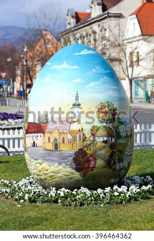 ZAGREB,CROATIA - MARCH 26, 2016 : Three easter eggs painted with technique naive by hand are placed on the Kaptol square in front of Zagreb Cathedral,Croatia.  - stock photo