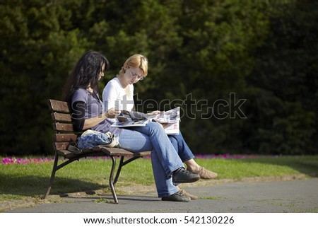 Zagreb, Croatia - May 29, 2011: Two girls reading newspaper and discussing news on a bench in a park in down-town Zagreb on May 29, 2011.