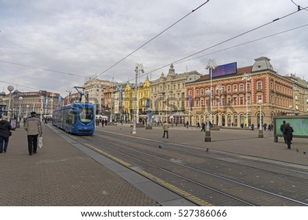 ZAGREB, CROATIA - Nov 18,2016 :People walk along city street with old houses and travel by tram in Zagreb, Croatia